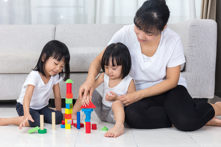 Foto de Asian Chinese mother and daughter playing blocks on the floor in the living room at home. - Imagen libre de derechos