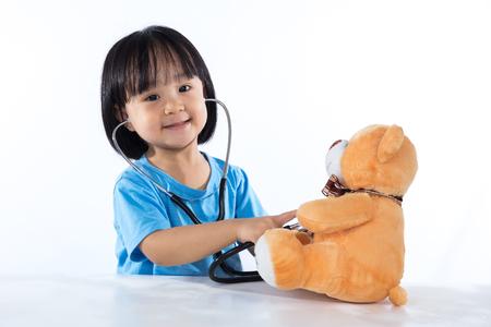 Foto de Happy Asian Chinese little doctor girl examine teddy bear in isolated white background. - Imagen libre de derechos