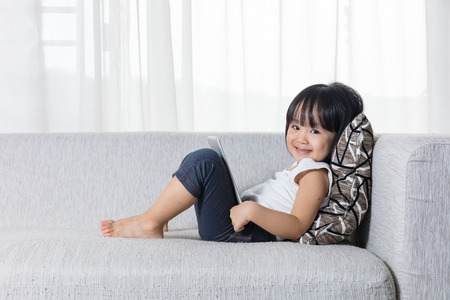 Photo for Happy Asian Chinese little girl lying on the sofa with tablet in the living room at home - Royalty Free Image