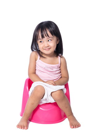 Foto de Asian chinese little girl sitting on chamberpot in isolated White Background - Imagen libre de derechos