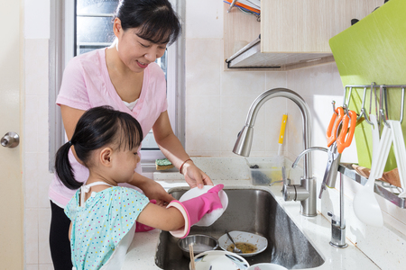 Foto de Asian Chinese little girl helping mother washing dishes in the kitchen at home - Imagen libre de derechos