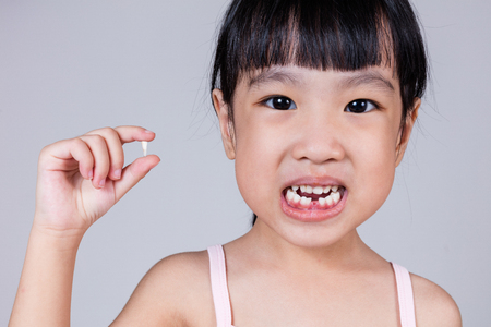 Photo pour Asian Chinese little girl holding her missing tooth in isolated white background - image libre de droit