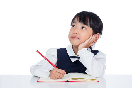 Photo pour Asian Little Chinese girl writing homework in isolated white background - image libre de droit