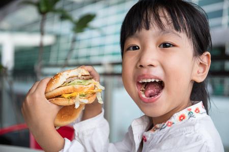 Foto de Asian Chinese little girl eating burger at outdoor cafe - Imagen libre de derechos