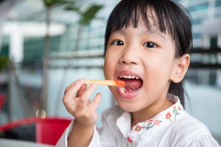Foto de Asian Chinese little girl eating French Fries at outdoor cafe - Imagen libre de derechos