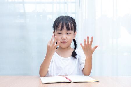 Foto de Asian little Chinese Girl doing mathematics by counting fingers at home - Imagen libre de derechos