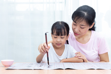 Photo for Asian Chinese mother teaching daughter practice Chinese calligraphy at home - Royalty Free Image