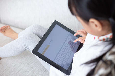 Photo pour Asian Chinese little girl sitting on the sofa playing digital tablet in the living room at home - image libre de droit