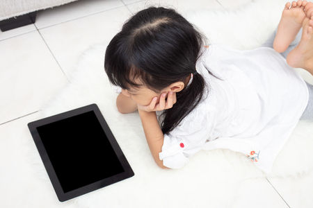 Foto de Asian Chinese little girl lying on the floor and playing tablet in the living room - Imagen libre de derechos