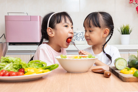 Foto de Asian Chinese little sisters making salad in the kitchen at home - Imagen libre de derechos
