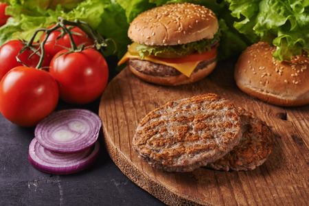 Photo for grilled patties on wooden background and burger  out of focus - Royalty Free Image
