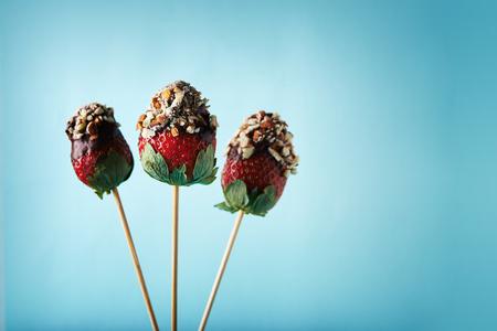 Foto de strawberries on sticks with chocolate and nuts on blue background - Imagen libre de derechos