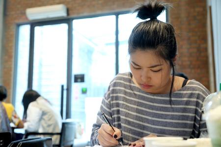 Photo pour The Asian woman learning japanese language in the coffee shop. - image libre de droit