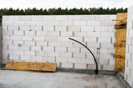 Photo pour The walls of the house are built with white stones and are in the form of ribbed stones, wooden formwork. - image libre de droit