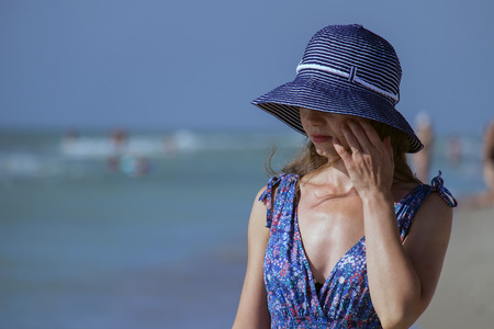 Foto per Young girl in a sundress stands on the beach and hides her eyes behind the brim of her hat - Immagine Royalty Free