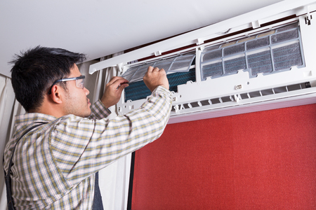 Photo pour Young man electrician cleaning air conditioning in a client house - image libre de droit