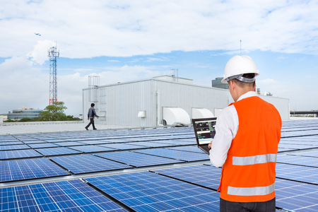 Photo pour Engineer on factory roof checking solar panels - image libre de droit