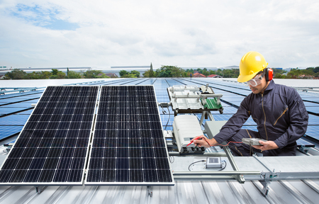 Photo pour Engineer maintenance solar panel equipment on factory roof - image libre de droit