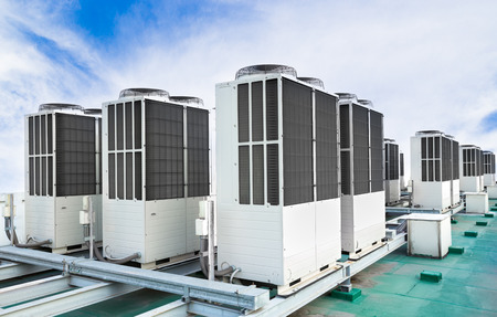 Foto per A row of air conditioning units on rooftop with blue sky - Immagine Royalty Free