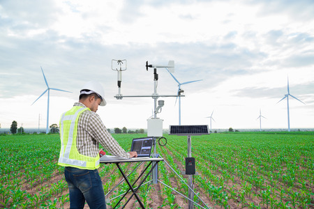 Foto per Engineer using tablet computer collect data with meteorological instrument to measure the wind speed, temperature and humidity and solar cell system on corn field background, Smart agriculture technology concept - Immagine Royalty Free