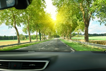 Photo pour View of the road and forest through the windshield of the car Sunshine - image libre de droit