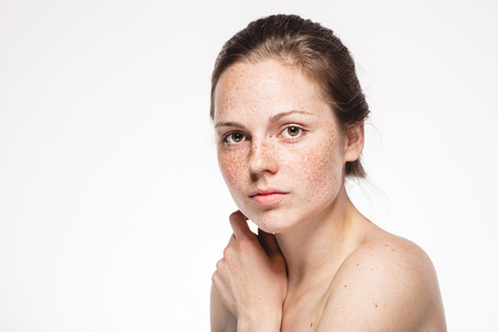 Photo pour Young beautiful freckles woman face portrait with healthy skin. Studio shot. Isolated on white. - image libre de droit