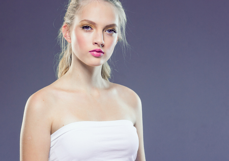 Foto de Beautiful blonde girl with long curly hair over purple background. Studio shot. - Imagen libre de derechos