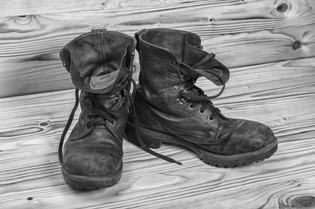 Foto de Old military boots on a wooden table in black and white. - Imagen libre de derechos