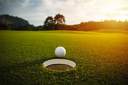 Photo pour selective focus. white golf ball near hole on green grass good for background with sunlight and lens flare effect - image libre de droit