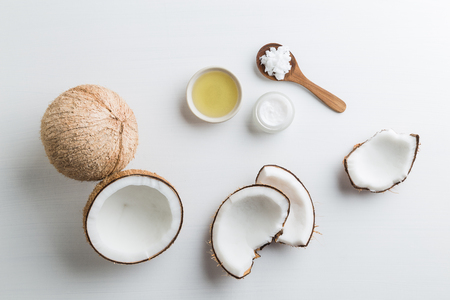 Photo pour Homemade coconut products on white wooden table background. Oil, scrub, milk and lotion from top view. Good for space and background. - image libre de droit