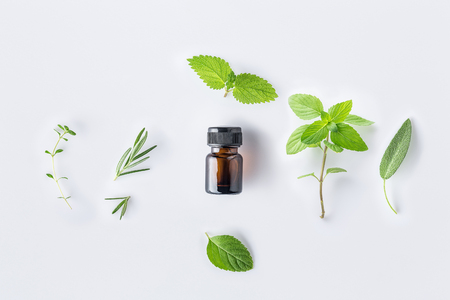 Photo pour Bottle of essential oil with fresh herbal sage, rosemary, thyme, lemon balm spearmint and peppermint setup with flat lay on white background - image libre de droit
