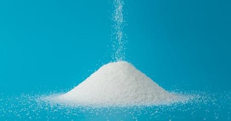 Photo pour Heap of sugar with pouring on blue background - image libre de droit
