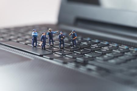 Foto de Miniature police squad protecting laptop computer. Technology concept - Imagen libre de derechos