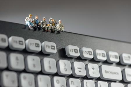 Photo pour Miniature workers sitting on top of keyboard. Technology concept. Macro photo - image libre de droit