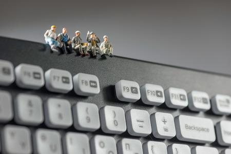 Foto de Miniature workers sitting on top of keyboard. Technology concept. Macro photo - Imagen libre de derechos