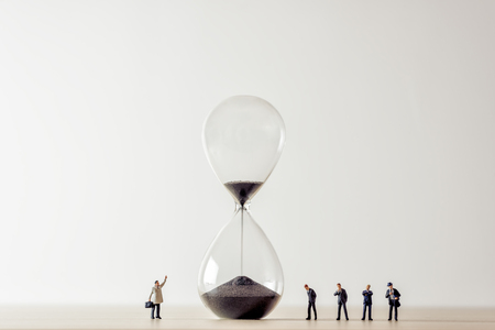 Photo for Conceptual image of business people looking at Hourglass. - Royalty Free Image