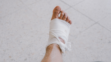 Photo for Bandaged leg after abrasion. Protect scratched body parts in travel. - Royalty Free Image