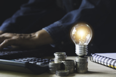 Photo pour Man working with a light bulb on stack of coins for business and accounting concept. - image libre de droit
