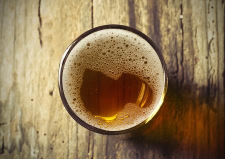 Foto de Beer barrel with beer glasses on table on wooden background - Imagen libre de derechos