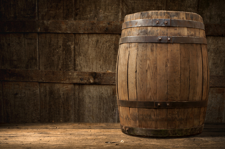Foto de Still life: old wooden pin of beer, glass of beer and wheat on the table in the cellar. - Imagen libre de derechos