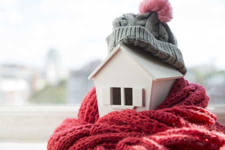 Foto de house in winter - heating system concept and cold snowy weather with model of a house wearing a knitted cap - Imagen libre de derechos