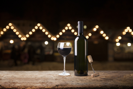 Photo pour red wine glass near bottle with light bokeh in background - image libre de droit