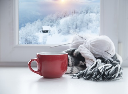 Photo for Winter background - cup with candy cane, woolen scarf and gloves on windowsill and winter scene outdoors. Still life with concept of spending winter time at cozy home with cold weather outdoors - Royalty Free Image