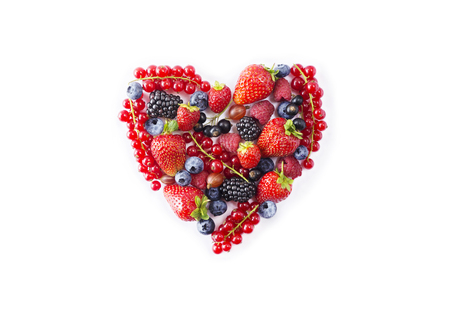 Photo pour Heart shape assorted berry fruits on white background. - image libre de droit