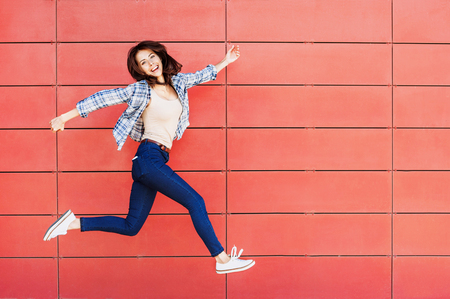 Foto de Joyful happy young woman jumping against red wall - Imagen libre de derechos