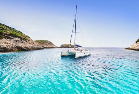 Photo for Beautiful bay with sailing boat catamaran, Corsica island, France - Royalty Free Image