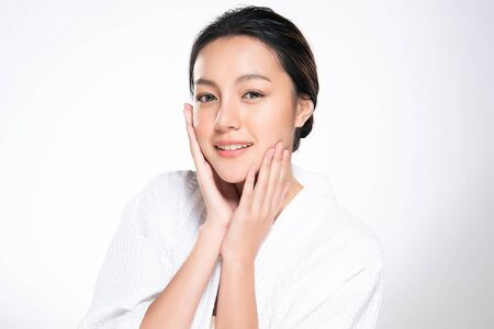 Foto de Beautiful young Asian woman touching soft cheek and smile with clean and fresh skin. Happiness and cheerful with, isolated on white background, Beauty and Cosmetics Concept, - Imagen libre de derechos