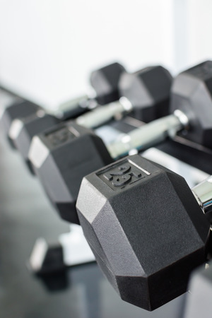 Close up rows of dumbbells on a rack in a gym