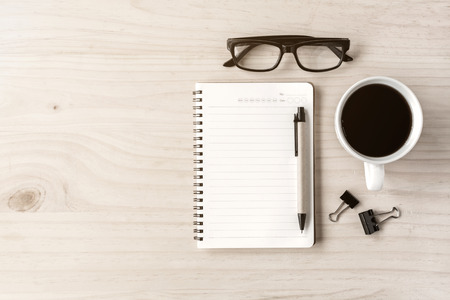 Foto de Cup of coffee with notebook on wooden desk - Imagen libre de derechos