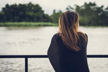 Foto de Lonely woman sitting and looking at the river - Imagen libre de derechos